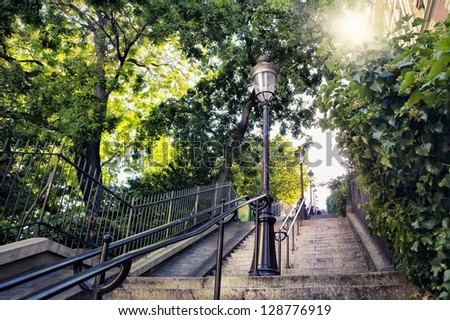 Typical Montmartre staircase in Paris, France with old street lamp and sunlight coming through the trees - stock photo