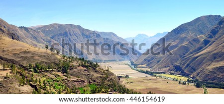 Typical mountain landscape. It is southern  American country -  Peru. Valley with the cultivated farmer fields is surrounded with high hills. Panoramic collage from several photos.