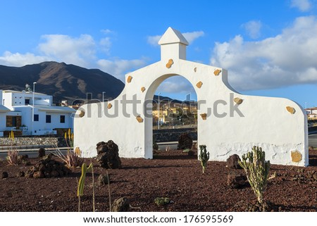 Typical municipality sign (white arch gate) in Gran Tarajal village with desert landscape in the background, Fuerteventura, Canary Islands, Spain - stock photo