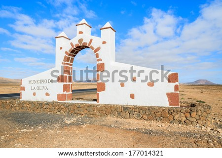 Typical municipality sign (white arch gate) in La Oliva town area with desert landscape in the background, Fuerteventura, Canary Islands, Spain  - stock photo