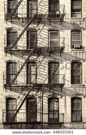 Typical New York City building with fire escape ladders - stock photo