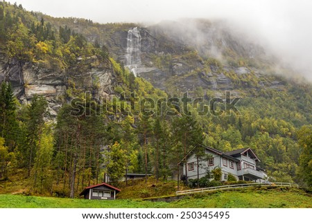 Typical norwegian wooden house with waterfall in the mist - stock photo