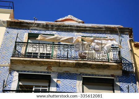 Typical old building in the centre of Lisbon (Portugal) with ceramic tiles (azulejos) and the linen and kitchen towels hanging to dry on the sun. - stock photo