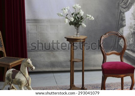 typical old photo studio with chair, table, flowers, rocking horse and a marble balustrade - stock photo