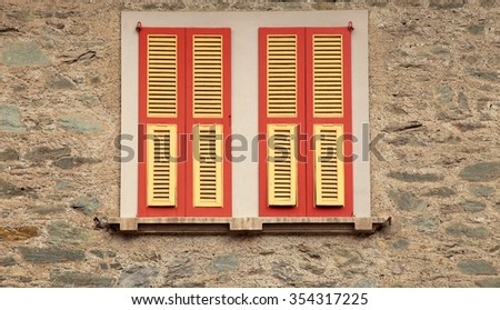 typical old red shutter windows in stone house, Italy. - stock photo
