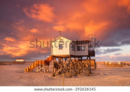 Typical pile house at the beach of St. Peter Ording north sea coast, Germany, sunrise - stock photo