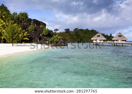 Typical Polynesian landscape - island with palm trees and small houses on water in the ocean and mountains on a background - stock photo