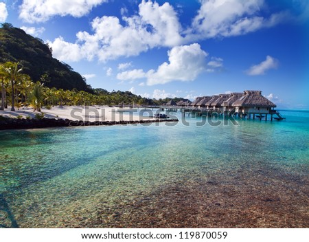 Typical Polynesian landscape - seacoast with palm trees and small houses on water. - stock photo