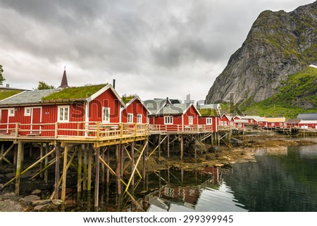 Typical red fishing huts called Rorbu  in town of Reine on Lofoten islands, Norway - stock photo
