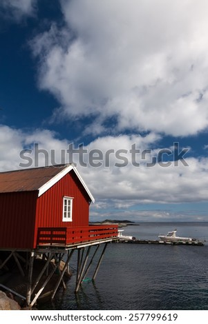 Typical red rorbu fishing hut in town of A village on Lofoten islands in Norway lit by midnight sun - stock photo
