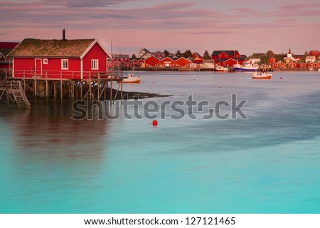 Typical red rorbu fishing hut in town of Reine on Lofoten islands in Norway lit by midnight sun - stock photo