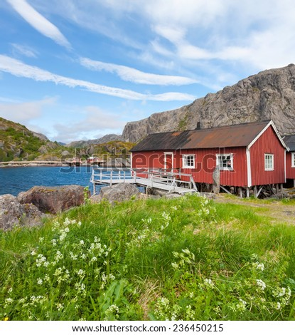 Typical red rorbu, fishing hut in village Nusfjord on Lofoten islands in Norway lit by midnight sun - stock photo