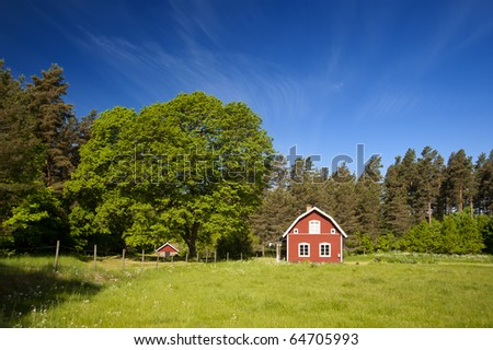 Typical red swedish cottage in idyllic landscape - stock photo