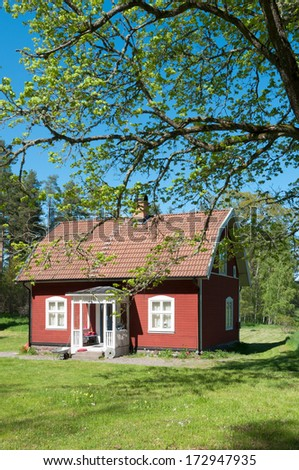 Typical red wooden house in Smaland, Sweden, in spring with fresh green foliage all around. - stock photo