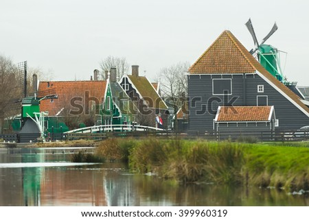 Typical rural settlement in old Holland with old windmills and calm river - stock photo