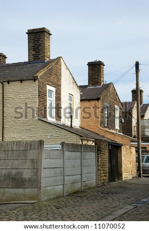 Typical scene of a cobbled street behind a row of terraced houses in a Lancashire mill town - stock photo