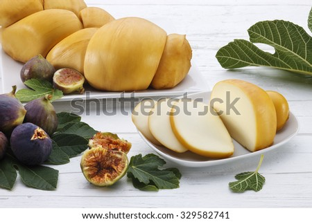 Typical sicilian smoked cheese called on a white dish with figs and fig leafs on a white wooden table. - stock photo