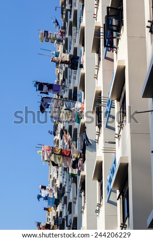 Typical Singapore public housing apartments where laundry is hung out to dry on bamboo poles from balconies. - stock photo