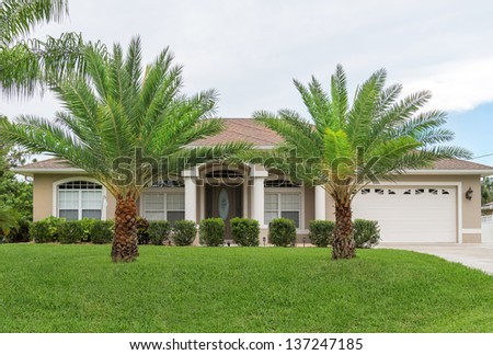 Typical Southwest Florida concrete block and stucco home in the countryside with palm trees, tropical plants and flowers and a bahia grass lawn.