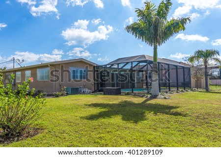 Typical Southwest Florida Concrete Block and Stucco Home with a Caged Pool in back.  Clear hurricane shutters on the windows and palm trees in the landscape. - stock photo