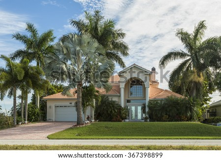 Typical Southwest Florida home in the countryside with palm trees, tropical plants and flowers, grass and pine trees. Inlaid pavement at the entrance. Florida - stock photo