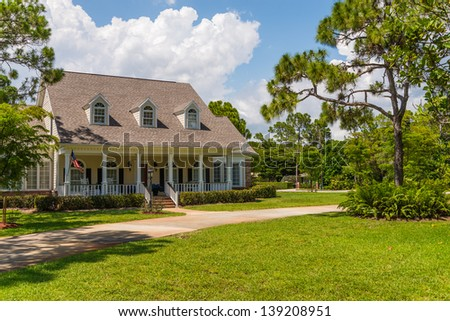 Typical Southwest Florida home in the countryside with palm trees, tropical plants and flowers, a bahia grass lawn and pine trees. - stock photo