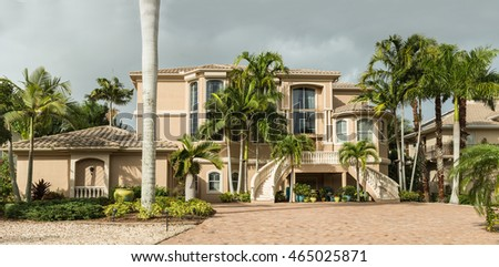 Typical Southwest Florida villa of concrete block with stucco with entrance for cars located in the green with palm trees, tropical plants and flowers, turf grass and pine trees. Florida.