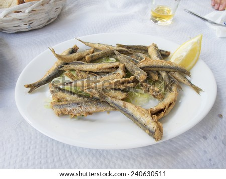 typical spanish fried sardines dish on white paper tablecloth restaurant - stock photo