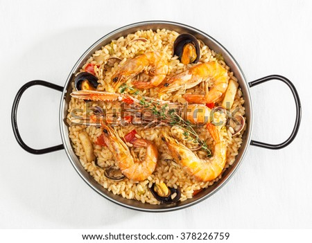 Typical Spanish seafood paella in pan on white background. Top view.