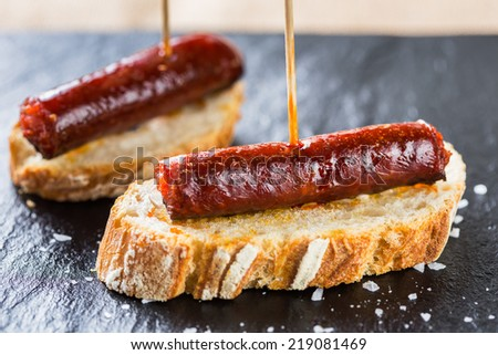 Typical spanish tapas: Delicious pork sausage called chistorra. - stock photo