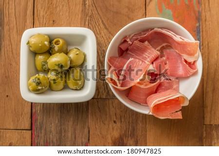 Typical Spanish tapas: serrano ham and marinated green olives - stock photo