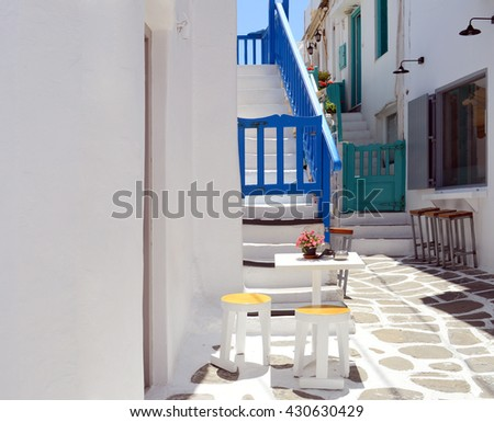 Typical street of greek traditional village with white walls and bougainvillaea, on Mykonos island, Greece - stock photo