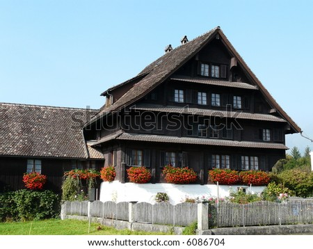 Typical swiss farmers house with geraniums (Switzerland)