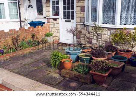 Typical tidy nice small front house garden, pots and plants, patio, drive way, exterior, front of house, main entrance of a house.