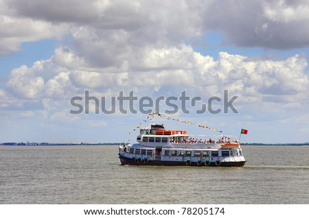 Typical touring boat in the river Tagus in Lisbon, Portugal - stock photo