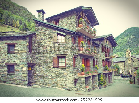 Typical traditional dark brick Andorra rural mountain houses in the village of Llorts near Andorra la Vella in the Pyrenees - old postcard / vintage look - stock photo