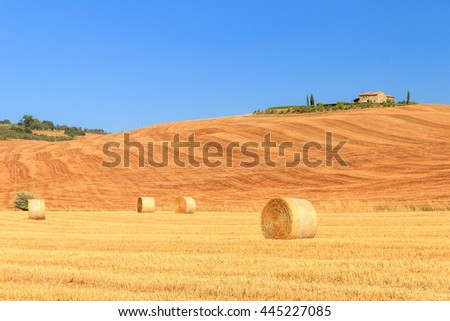 Typical Tuscan hill landscape with a farm and yellow hay fields with bales in summer with a blue sky - stock photo