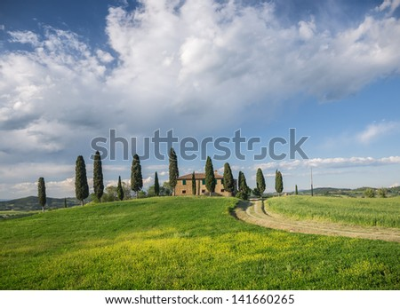Typical Tuscan style farmhouse in the Val d'Orcia under a dramatic sky - stock photo
