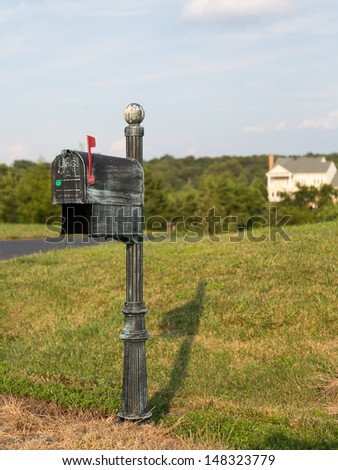 Typical US post or mail box with red flag raised to indicate that mail is ready for collection outside single family home in suburbs of Virginia USA - stock photo