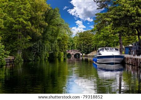 typical vacation hire cruiser moored on the tree lined banks of the river wensum in the city of norwich, norfolk broads with the historic bishop bridge in the background - stock photo