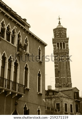 Typical Venetian building and leaning bell tower at backgrounds. Cloudy winter day. Venice, Italy. Aged photo. Sepia. - stock photo