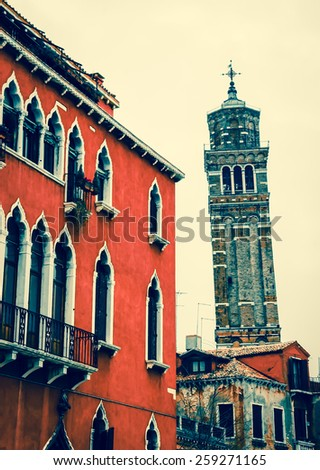 Typical Venetian building and leaning bell tower at backgrounds. Cloudy winter day. Venice, Italy. Toned photo. - stock photo