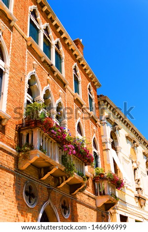 Typical Venetian house walls, decorative balcony with flowers, detail - stock photo