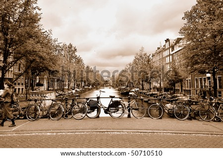 Typical view of the Amsterdam center with bicycles on a bridge across a canal in overcast spring day. Sepia toned image. - stock photo