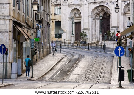 Typical view of the streets of Lisbon, capital of Portugal, steeply going up, early morning, still empty, with the rails for the tramway 28 idle lying in the stones - stock photo