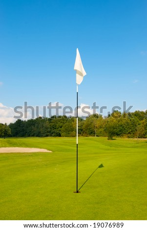 Typical view on a golf course. A generic white flag marking the hole. With a blue sky in the background.