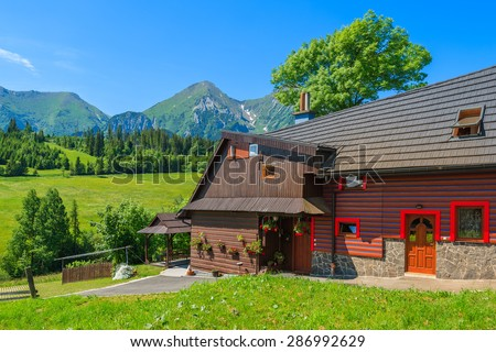 Typical wooden house on green meadow with Tatry Bielskie Mountains in background in summer, Slovakia - stock photo