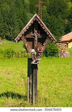 Typical wooden wayside shrine with jesus on cross in Italian alps. Trentino Alto Adige, Italy
