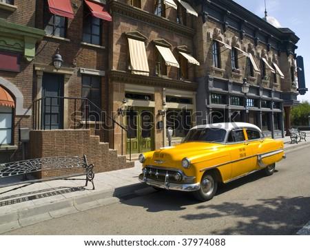 Typical yellow cab of the 50s, 60s in a old american town - stock photo