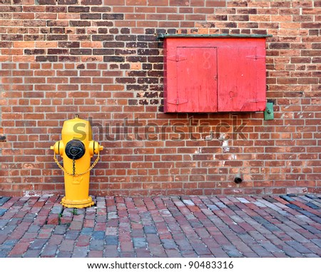 Typical yellow fire hydrant and box for fire-fighting equipment. - stock photo